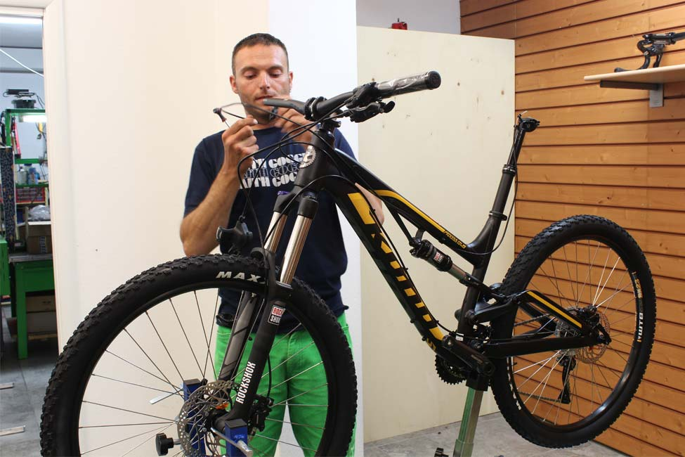 Tecnico che aggiusta una bici nel bike service di Defox