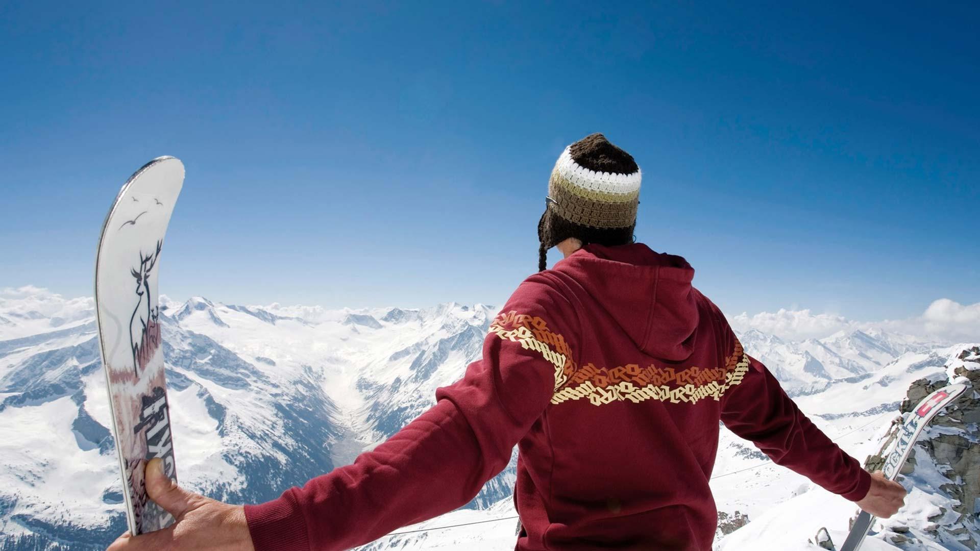 Ragazzo che guarda il panorama di Livigno con gli sci in mano